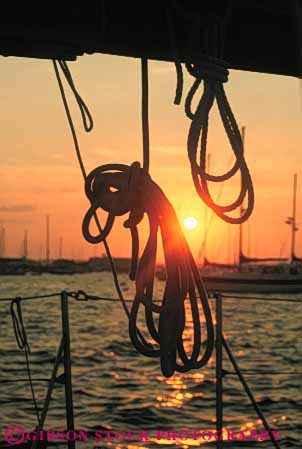 Stock Photo #7351: keywords -  boater boating boats coast coastal coil coiled dawn dusk evening line lines manmade marine maritime mood moody motorboat ocean rope ropes sail sailboat sea shore shoreline silhouette silhouettes structure sun sunrise sunset vert warm water yacht