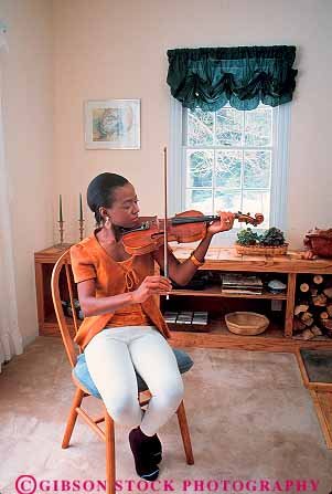 released African American woman playing violin at home ...