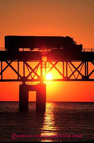 Stock Photo #1823: keywords -  bridge commerce industry mackinac michigan orange shipping silouette sun sunrise sunset transportation truck trucking vert warm