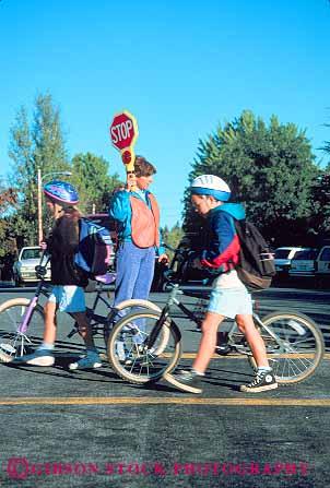 Children Walking Bikes To School In Crosswalk Near Crossing Guard