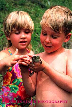 Stock Photo #2001: keywords -  amphibian animal boy child children examine frog gentle girl hold look model outdoor released study touch vert wet