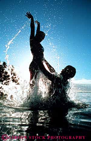 Stock Photo #3450: keywords -  close couple couples fun help joy jump lift play released share silhouette splash summer swim together tropic tropical vacation vert warm