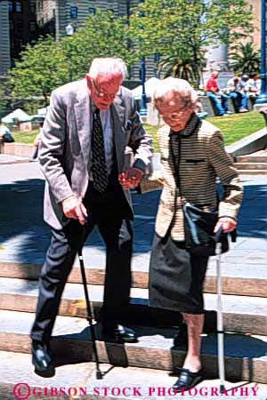 Stock Photo #6116: keywords -  assist canes careful caution citizen couple elderly help mature old senior seniors slow slowly step steps timers vert walk with