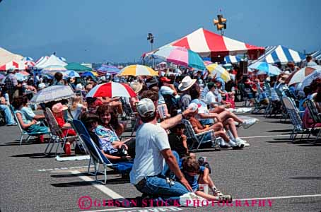 Stock Photo #4989: keywords -  air array audience crowd crowded gather gathered gathering grouped horz hot lots many multitude observe pavement people see shade show summer sun sunny together umbrella umbrellas watch